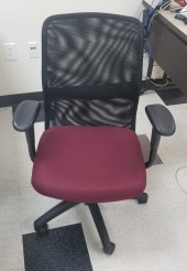 Mesh task chair with maroon fabric seat with arms